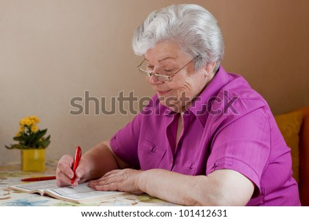 pensioner puzzles and smiles with reading glasses - stock photo