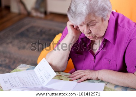 Pensioner read countless papers and is very focused - stock photo