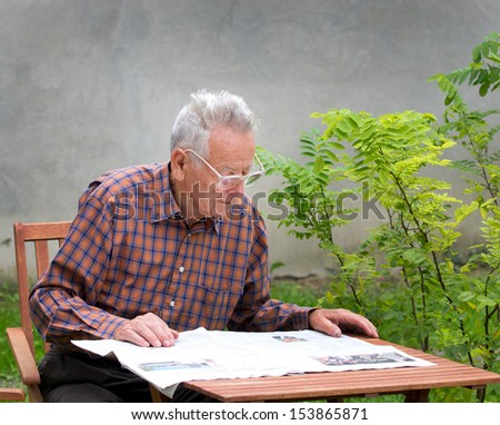 Pensioner reading newspaper in garden - stock photo