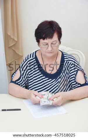 Pensioner READS PAPER AND COUNTING MONEY.Old woman with money.PENSION IN THE HANDS OF ELDERLY WOMAN.The old woman sitting at the table,read the paper , count the money.Pleasing appearance older women