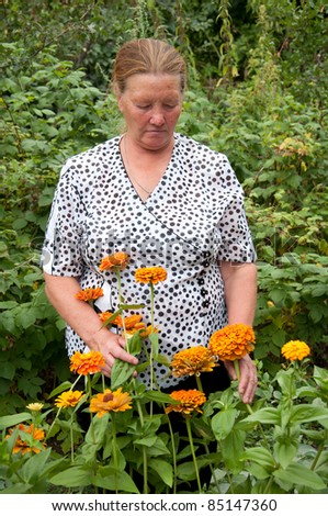Pensioner takes care of the flowers in the garden at the cottage - stock photo