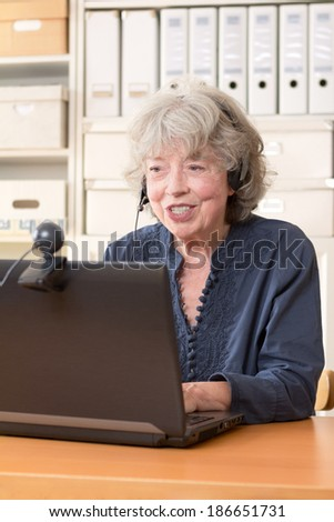 Pensioner telephoning with her family via skype, copy space - stock photo