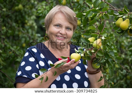Pensioner woman under pear tree
