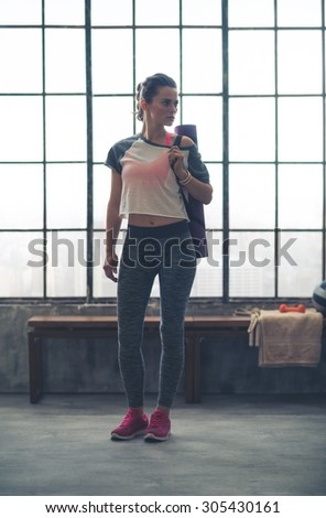 Pensive, a fit woman is standing in front of a wooden bench in a loft gym. With her yoga mat over one shoulder, she is looking off to the side, thinking. - stock photo