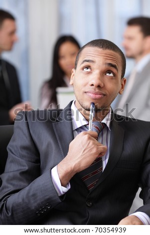 Pensive african-american businessman with his team working behind - stock photo