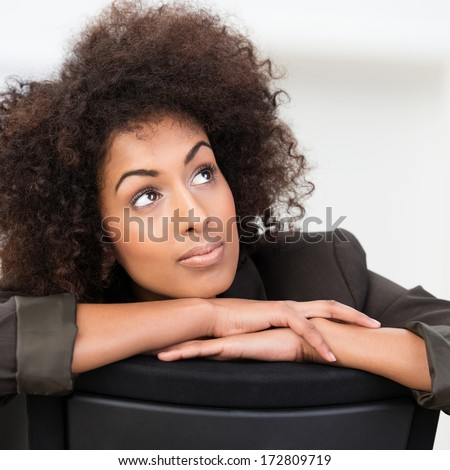Pensive African American businesswoman with curly afro hair sitting with her arms on the back of the chair staring up into the air in contemplation - stock photo
