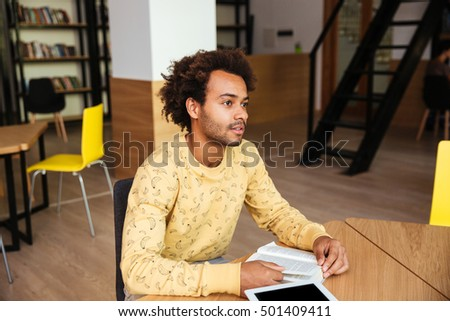 Pensive african american young man reading book and thinking at the table in library