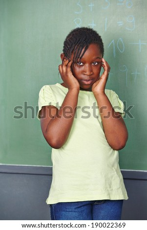 Pensive african girl in front of chalkboard in elementary school - stock photo