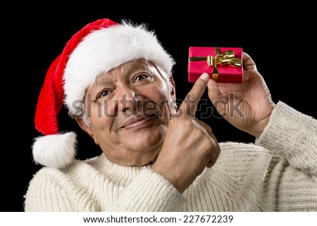Pensive aged man in warm pullover and red Santa Claus cap. He is pointing his right index finger at a small, red, wrapped gift held on eye-level in his left hand. Isolated on black. Gift-giving theme. - stock photo