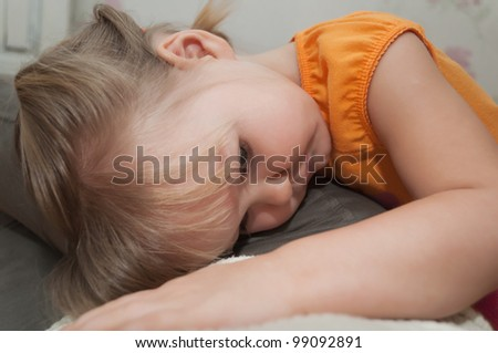Pensive  and sad baby girl is lying on her mother - stock photo