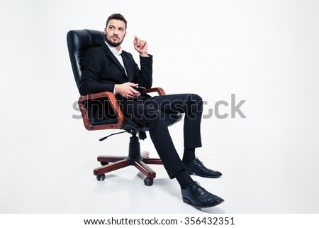 Pensive angry bearded business man in formalwear sitting in black office chair and holding cellphone over white background