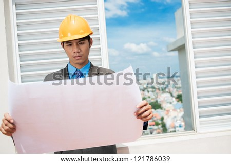 Pensive architect studying the housing project - stock photo