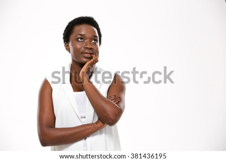 Pensive attractive african american young woman standing and dreaming over white background - stock photo