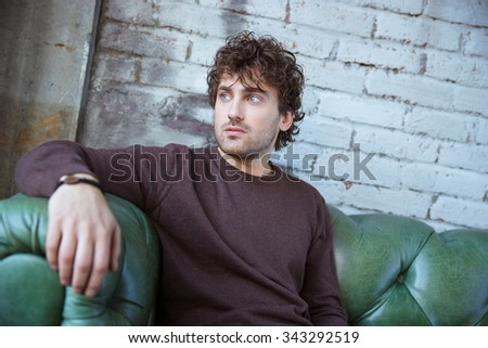 Pensive attractive thoughtful curly young man in brown sweetshirt thinking on green leather sofa alone - stock photo