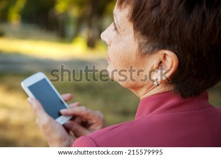 pensive attractive woman 50 years with mobile phone in hand - stock photo