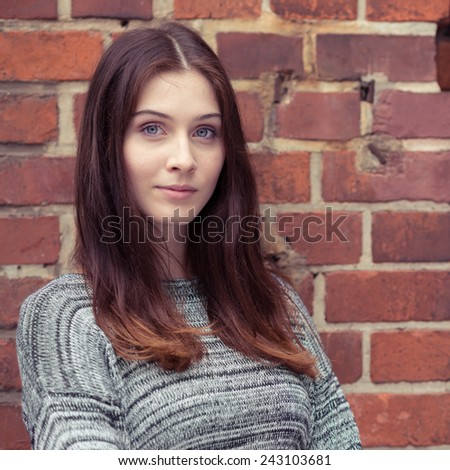 Pensive attractive young woman looking at the camera with a serious expression as she leans against an exterior face brick wall - stock photo
