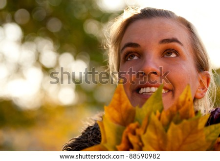 Pensive autumn woman holding leaves and smiling