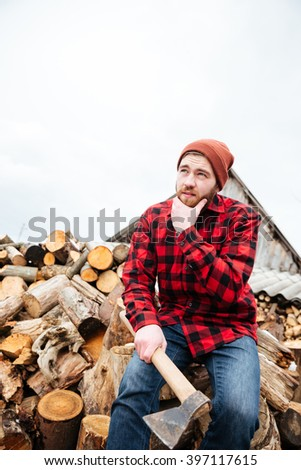 Pensive bearded young man in plaid shirt and hat with axe sitting on logs and thinking  - stock photo