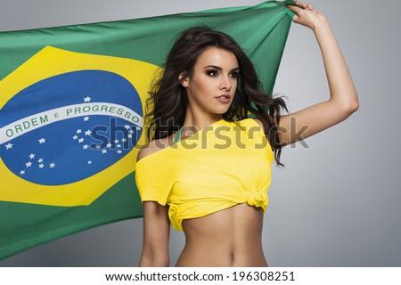 Pensive beautiful brazilian female football fan - stock photo