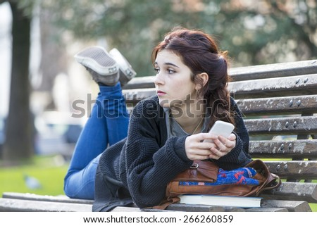 Pensive beautiful girl lying on old wood bench and holding phone looking away, adolescense lifestyle concept. - stock photo