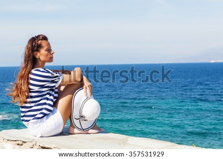 Pensive beautiful woman sitting and looking at open sea.Copy space - stock photo
