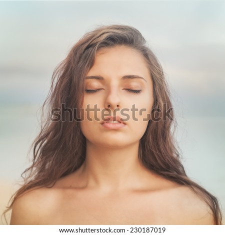 pensive beautiful woman with her eyes closed against the evening sky - stock photo