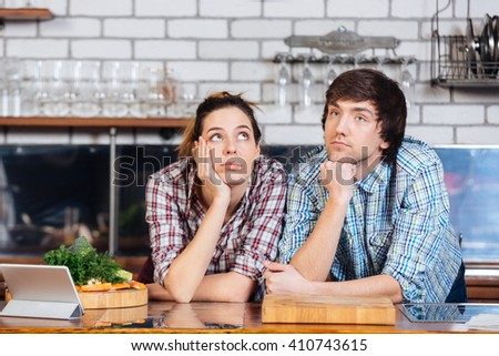 Pensive beautiful young couple thinking on the kitchen - stock photo