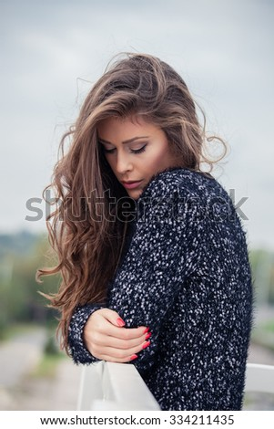 pensive beautiful young long hair woman in cardigan, outdoor autumn day portrait - stock photo