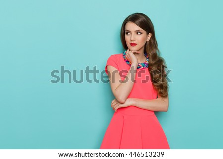 Pensive beautiful young woman in pink mini dress posing with hand on chin and looking away. Three quarter length studio shot on turquoise background. - stock photo