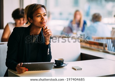 Pensive black businesswoman using tablet computer in coffee shop - stock photo