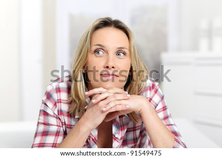pensive blond woman at home on sofa - stock photo