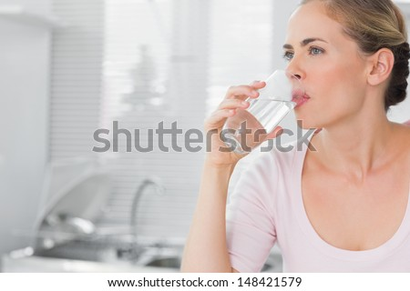 Pensive blond woman drinking water in her kitchen - stock photo