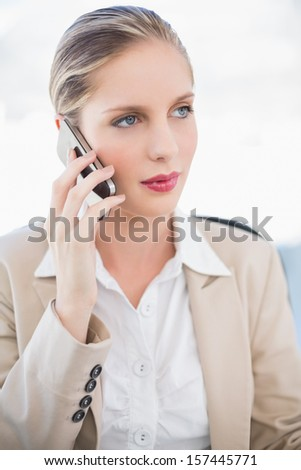 Pensive blonde businesswoman having a phone call posing in bright office - stock photo