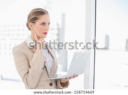Pensive blonde businesswoman using laptop in bright office
