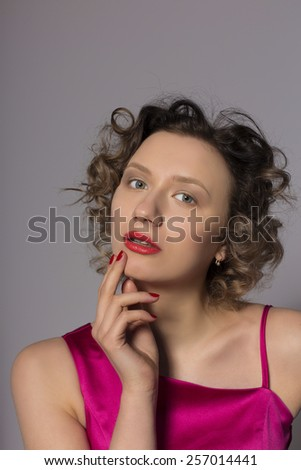 pensive blonde on a gray background in studio - stock photo