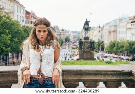 Pensive bohemian woman tourist in knitted shawl and white blouse standing Wenceslas Square, Prague. Tourism travel concept. - stock photo