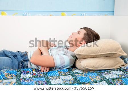 pensive boy lying on the sofa - stock photo
