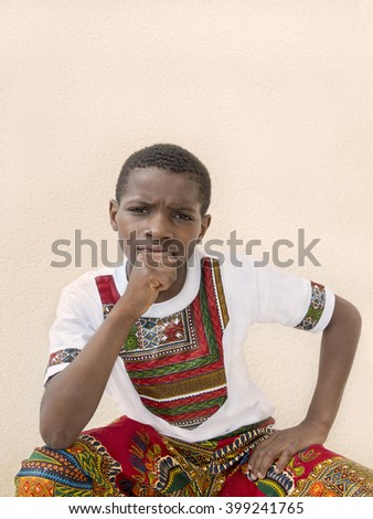 Pensive boy seated in front of a wall, ten years old