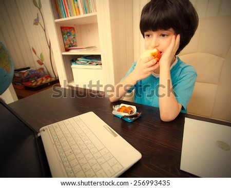 pensive boy sitting at a table with a laptop and eating apple. instagram image retro style - stock photo
