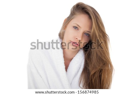 Pensive brunette in bathrobe looking at camera on white background