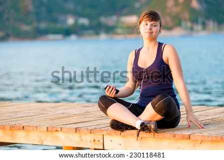 Pensive brunette with the player on the pier at dawn - stock photo