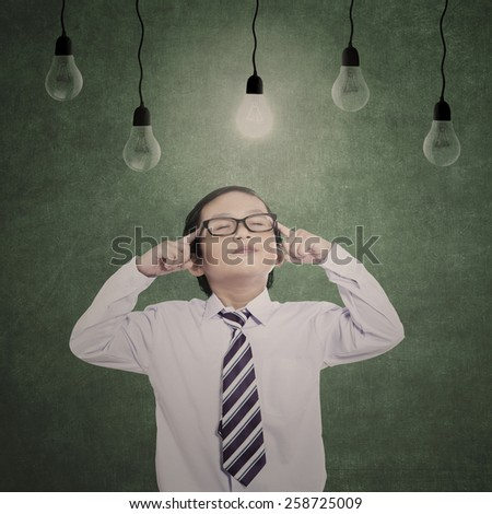 Pensive business kid under lit bulbs with eyes closed in class - stock photo