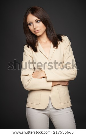 Pensive business woman in beige suit standing with folded hands looking down  - stock photo