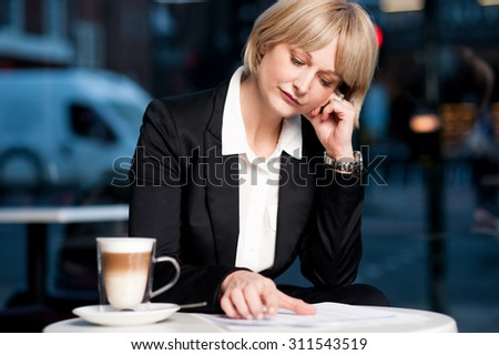 Pensive business woman looking into report at cafe - stock photo