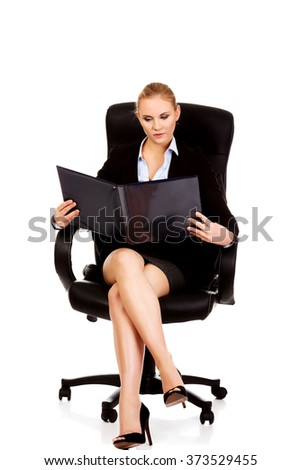 Pensive business woman sitting on armchair and reading notes - stock photo