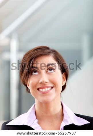 Pensive business woman smiling at the office - stock photo