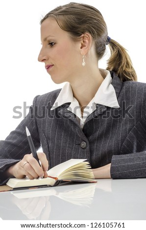 Pensive business woman thinking what to write in her diary. Isolated over white background. - stock photo