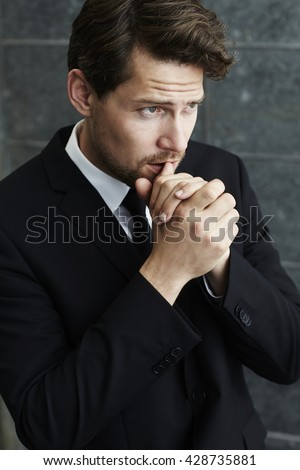 Pensive businessman in black, looking away - stock photo