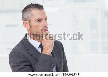 Pensive businessman in bright office looking away - stock photo