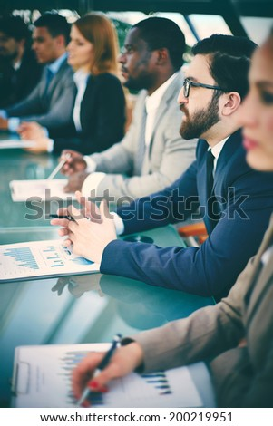 Pensive businessman listening to speaker at seminar surrounded by other listeners